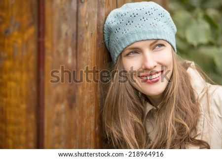 Beautiful autumn woman over wooden background happy smiling dreaming looking to the side #218964916