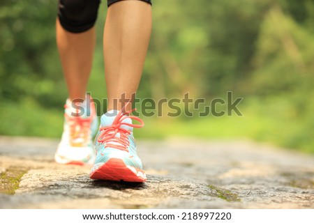 young fitness woman legs walking on forest trail  #218997220