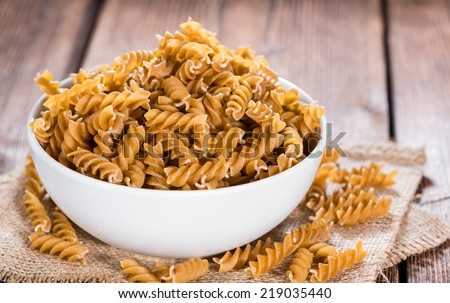 Portion of uncooked Wholemeal Fussili on wooden background #219035440