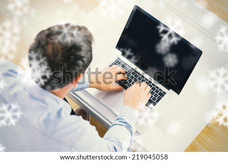 High angle view of casual man using laptop against snowflakes #219045058