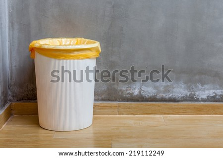 The white plastic bin with orange bag on wooden floor with exposed cement background, for cleaning and recycle. #219112249