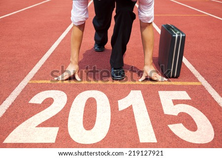 happy new year 2015. businessman preparing for running with briefcase Royalty-Free Stock Photo #219127921