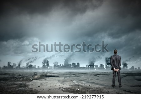 Rear view of businessman looking at ruins of city Royalty-Free Stock Photo #219277915