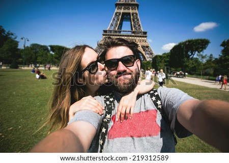 Happy smiling couple kissing and taking selfie photo in front of Eiffel Tower in Paris while traveling across France