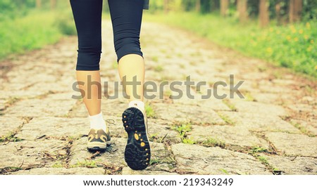 young fitness woman legs walking on forest trail  #219343249