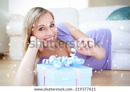 Composite image of Delighted blond woman holding a present lying on the floor against snow