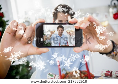 Hand holding smartphone showing photo against snow #219382618