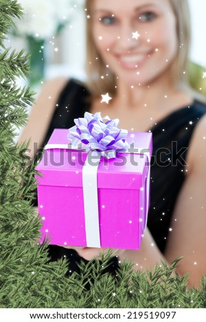 Composite image of a Blond woman opening a gift sitting on a sofa against twinkling stars