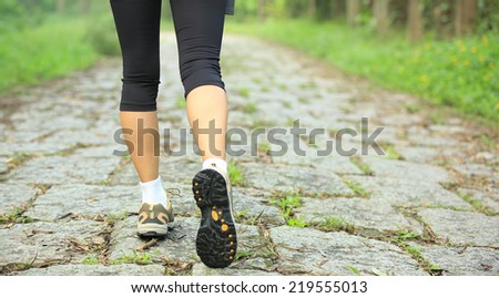 young fitness woman legs walking on forest trail  #219555013