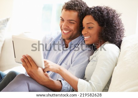 Young Couple Sitting On Sofa Using Digital Tablet #219582628