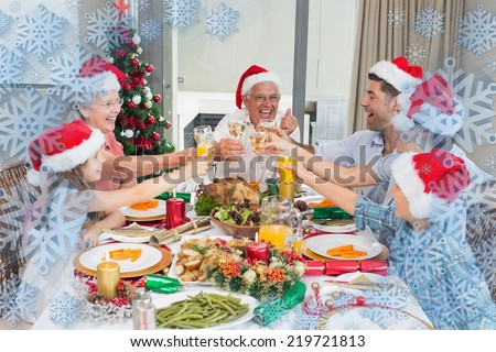 Family in santas hats toasting wine glasses at dining table against snowflake frame #219721813