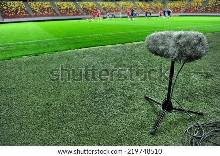 Professional sport microphone on a football field with players training in the background