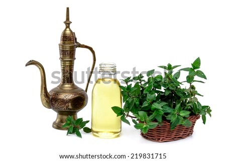 Spa and wellness setting with oil essence, mint  and vintage indian pitcher  with place for text. Relax and treatment therapy. White background. Selective focus. Close up. #219831715