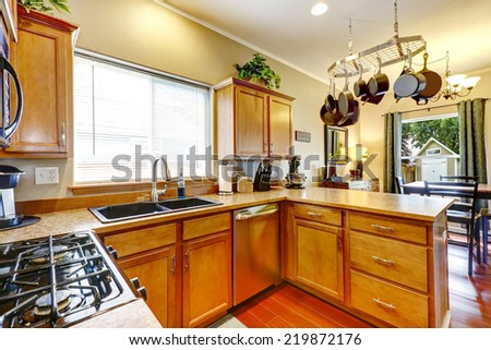 Kitchen interior with steel appliances and hanging pot rack #219872176