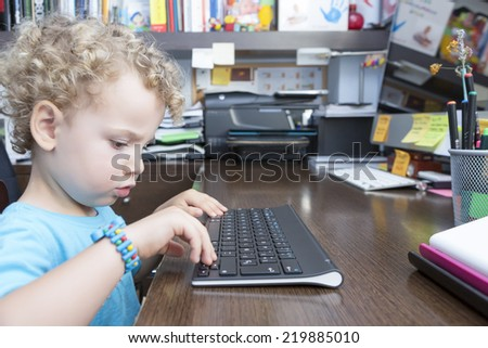 child using a computer wireless keyboard sitting on a desk at the office - focus on the face #219885010