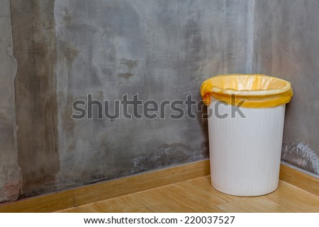 The white can bin at the corner on wooden floor with exposed cement background, for cleaning and recycle. #220037527