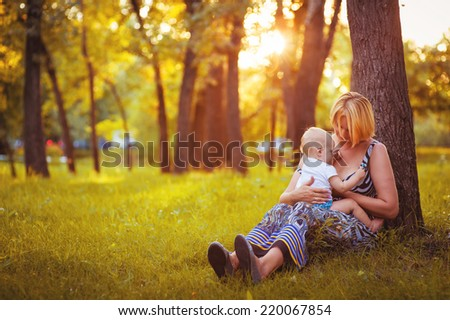 Young mother breast feeding young adorable baby in park.. The baby sucks a breast. The mother feeds the young baby in the countryside in the sunlight at sunset. Breast feeding. #220067854