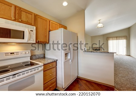 Kitchen area in empty house. White appliances and wooden cabinet. #220152070