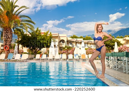 Beautiful slim girl standing in a swimsuit at the pool #220252600