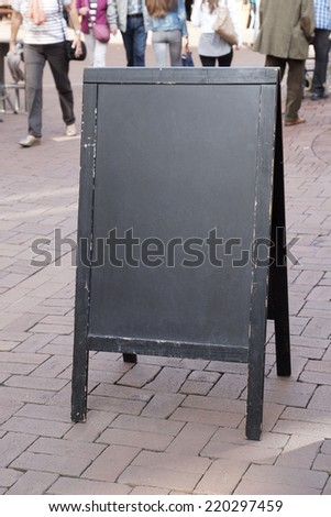 blank blackboard advertising street sign with unrecognizable pedestrians in the background