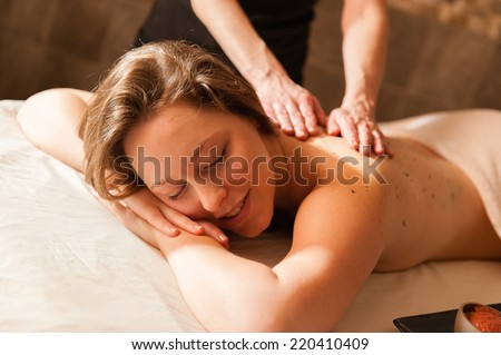 Beautiful young woman in a spa receiving a massage. #220410409