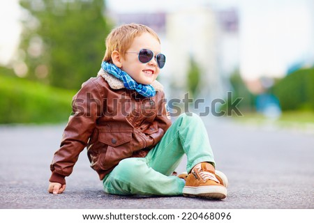 cute stylish boy in leather jacket sitting on the road Royalty-Free Stock Photo #220468096