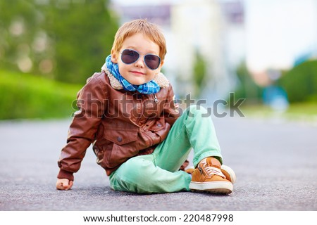 cute stylish boy in leather jacket sitting on the road Royalty-Free Stock Photo #220487998