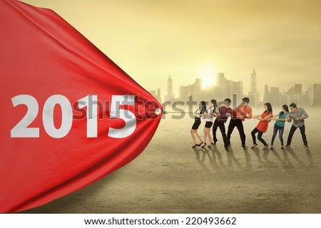 Young business people try to pull number 2015, symbolizing an effort for progress in 2015 Royalty-Free Stock Photo #220493662