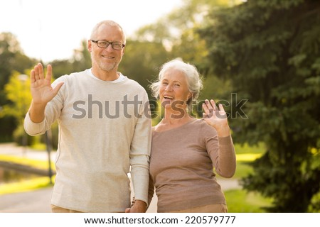 family, age, tourism, gesture and people concept - senior couple waving hands in city park #220579777