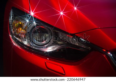 Headlights and hood of sport red car with silver stars #220646947
