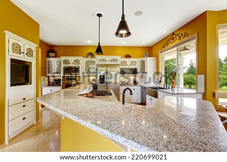 Farm house interior. Luxury kitchen room in bright yellow color with big island and granite top.