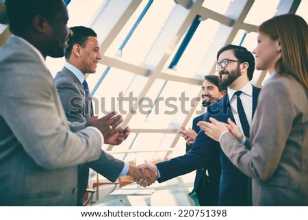 Group of business people congratulating their handshaking colleagues after signing contract Royalty-Free Stock Photo #220751398