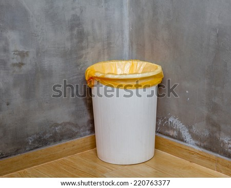 The white can bin at the corner on wooden floor with exposed cement background, for cleaning and recycle. #220763377