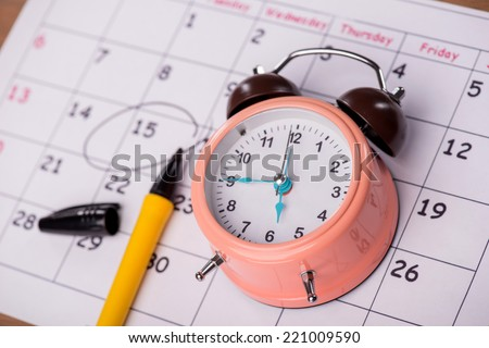Close-up top-view photo of calendar with a datum circled with a black marker lying on it, with selective focus on an alarm clock, concept of time management at work