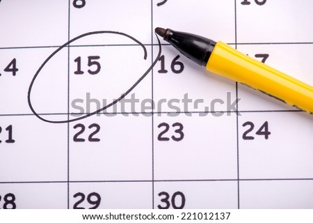 Close-up top-view photo of calendar with a datum circled with a back marker, concept of time management at work