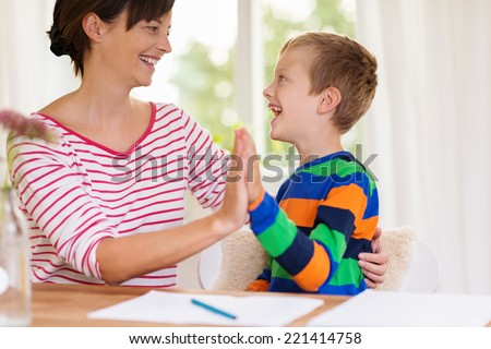 Young boy laughing with his mother or teacher and clapping hands as they sit together at a table or desk #221414758