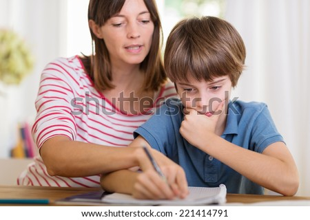 Young mother doing homework with her son pointing to something written in his notebook as he stares thoughtfully at the page #221414791