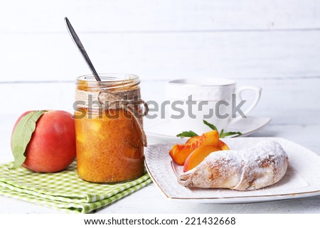 light breakfast with cup of tea and homemade jam on wooden table #221432668