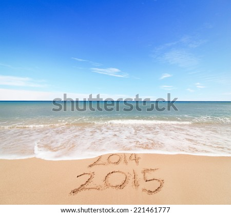 New Year 2015 is coming concept - inscription 2014 and 2015 on a beach sand, the wave is covering digits 2014 Royalty-Free Stock Photo #221461777