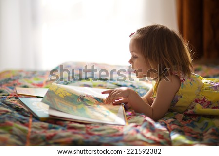 A little cute girl in a yellow dress reading a book lying on the bed #221592382