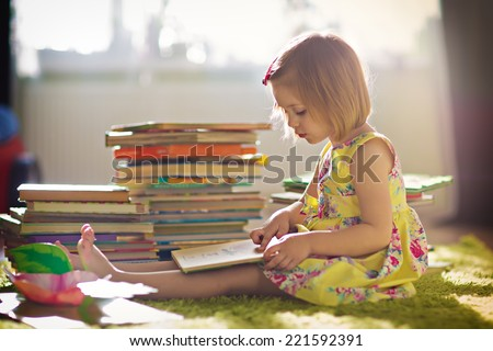 A little cute girl in a yellow dress reading a book sitting on the floor #221592391