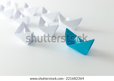 Leadership concept using blue paper ship among white Royalty-Free Stock Photo #221682364