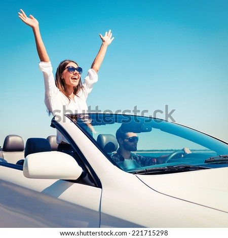 Couple in convertible. Happy young couple enjoying road trip in their convertible while woman raising arms and smiling  #221715298