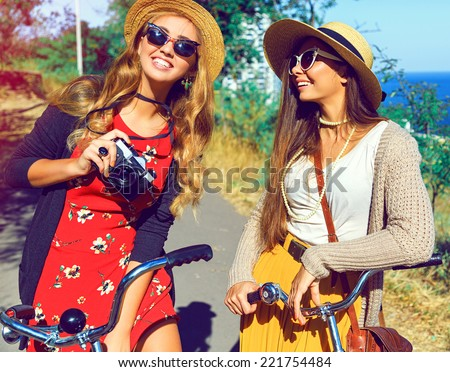 Outdoor fashion portrait of two hipster girls smiling laughing and have perfect free day together, walking with retro bicycles, taking pictures on retro camera, wearing stylish vintage outfits .