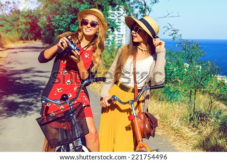 Pretty blonde girl showing pictures from her retro vintage hipster camera to her best friend, have nice day together walking with bicycles in the park near sea side.