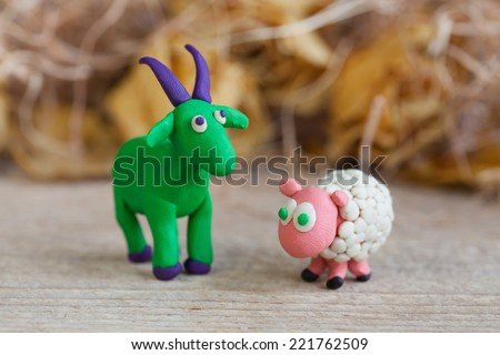 Plasticine world - little homemade green goat with purple horns and hooves and sheep stands on a wooden floor, selective focus and place for text