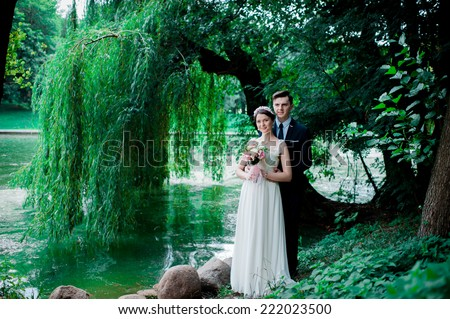 Wedding shot of bride and groom in park. summer nature outdoor. Beautiful bride and groom is enjoying his wedding day.  They kiss and hug each other #222023500