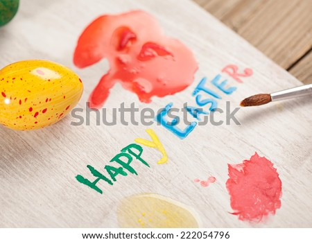 """Wooden board with color stains and """"Happy Easter"""" written on it with egg color. #222054796"""