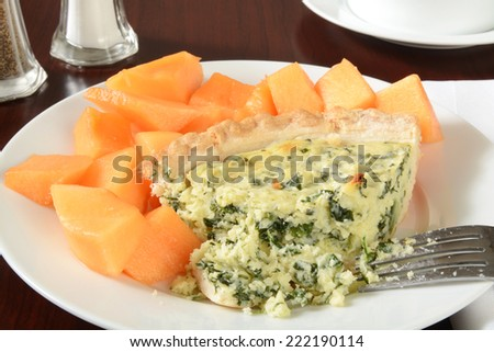 A slice of quiche Florentine with diced cantaloupe #222190114