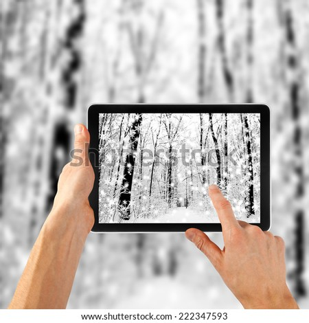 tablet ipades computer in hand on the winter forest backgrounds.